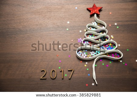 Sigh symbol Christmas Tree from a lot colorful confetti, lace and red star toy on old retro vintage style wooden texture background Empty copy space for inscription Idea of merry new year 2017 holiday #385829881