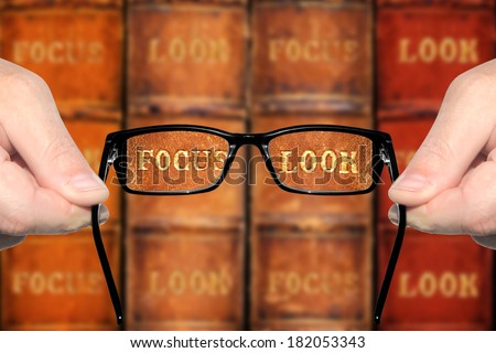 Sight test - optometrist's hands holding and offering eye glasses for the sharp look (in focus) on the books against the indistinct ( unsharp, not in focus) background. Concept of visual acuity return