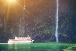 Sightseeing boat carrying tourist people approaches great waterfall in Milford Sound. Beautiful scenic cruise through Fiordland National Park in South Island of New Zealand.