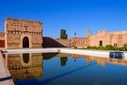 Sightseeing of Morocco. El Badi Palace in Marrakech medina with reflection in water pond. A popular architectural and tourist attraction.
