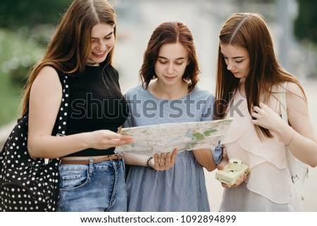 Sightseeing, travel, vacation, city tour. Happy women tourists traveling in the city using touristic map #1092894899