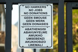 sign against a gate with words or text no hawkers, no jobs, no donations in English, Afrikaans and Xhosa concept no begging and economic downturn