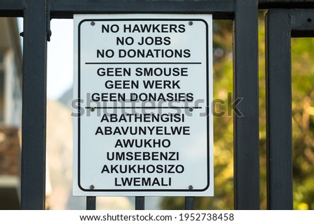 sign against a gate with words or text no hawkers, no jobs, no donations in English, Afrikaans and Xhosa concept no begging and economic downturn  Photo stock ©