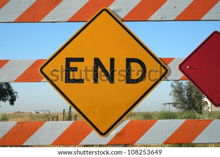 Sign and barrier mark the end of a road and suggest a visual concept of an ending