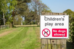 Sign at the entrance of a children's play area saying that dogs are not allowed.