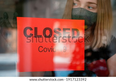 Sign Closed covid 19 lockdown on front entrance door as new normal shutdown in restaurant. Woman in protective medical mask gloves hangs closed sign on window of empty cafe. Small business crisis. Photo stock ©