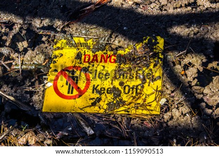 Sign Danger! Ice unstable! Keep Off! in mud and debris #1159090513