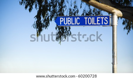 Sign directs to public toilets, with leaves and copy space