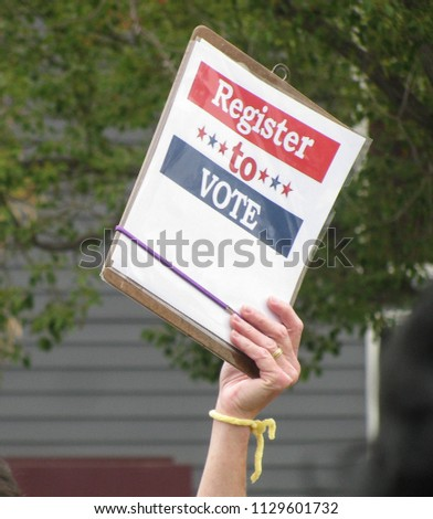 Sign displayed by hand at a political rally encourages people to register and vote in the crucial November 2018 U.S. congressional elections. General image for the power of democracy.