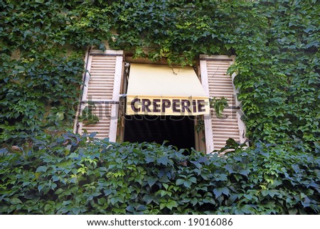 Sign for a French Creperie above a window in a wall grown with ivory