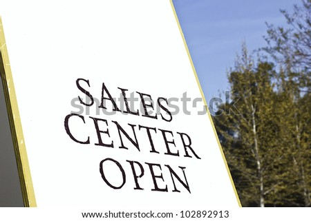 Sign for a sales center that is open in residential district.