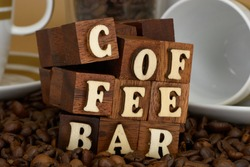 Sign for coffee bar in wooden letters for background, kitchen or shops. With cups and coffee beans in different views and styles. Letter words - fuzzy view cold white and white design