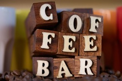 Sign for coffee bar in wooden letters for background, kitchen or shops. With cups and coffee beans in different views and styles. Letter words - Fuzzy view with colored cups modern cold color