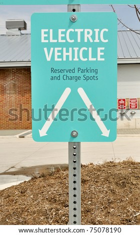 Sign for designated parking spot and charge point for electric vehicle