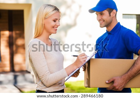 Sign here please! Smiling young delivery man holding a cardboard box while beautiful young woman putting signature in clipboard