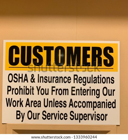 Sign in business instructing customers to not enter work area unless accompanied by employee #1333960244