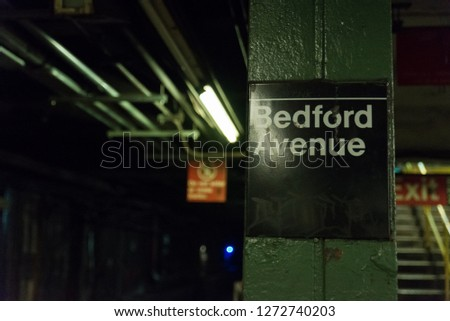 Sign inside the bedford avenue l train station in brooklyn new york  near the williamsburg hipster area where there is a high amount of art and culture. a light is shining on the sign and the subway  Stock fotó ©