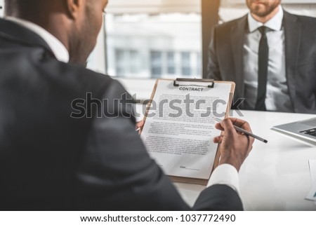 Sign it. Two business partners are sitting at table opposite. African man is holding contract and reading it while going to put his signature. Focus on sheet of paper