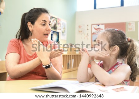 Sign language teacher in a extra tutoring class with a deaf child girl using American Sign Language. #1440992648