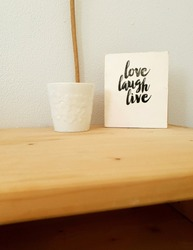 Sign, Live Laugh Love on wooden shelf, modern decoration in retro home clean interior