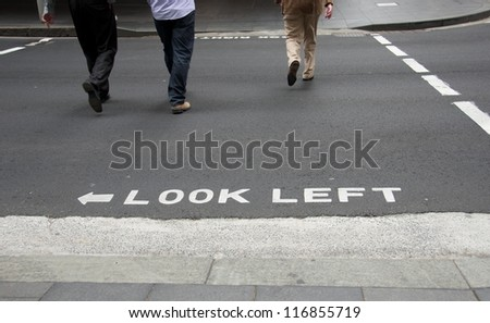 Sign Look left written on the street in Australia (or Great Britain) with people legs in background. Street scene.  Road sign. Transport system. Transport sign. Body part.