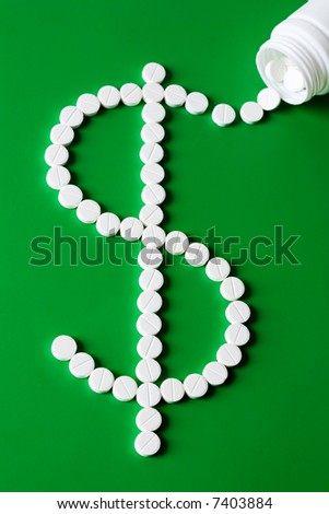 Sign of dollar made up out of white tablets on the green background