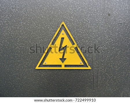Sign of high voltage on a gray metal surface. #722499910
