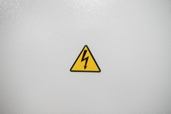 Sign of high voltage, screwed to a metal structure in gray.