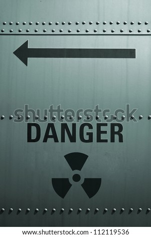 Sign of radioactive danger on the metal wall.