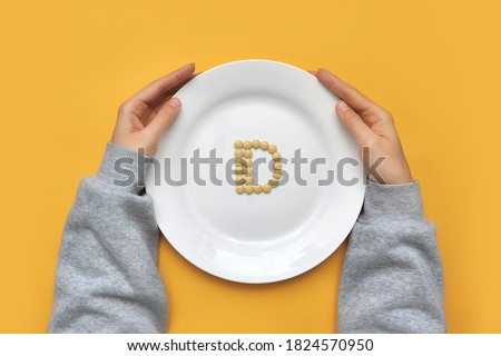 """Sign of vitamin """"D"""" out of pills on a white plate. Vitamin """"D"""" deficiency in humans"""