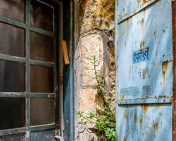 Sign on  a rusty blue door saying in Hebrew Veahavta,AND YOU SHALL LOVE in Jerusalem Israel