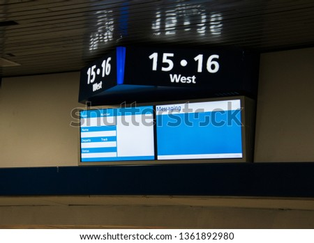 Sign on a wall near the ceiling Top part shows track numbers and the two screens below is a template for train information