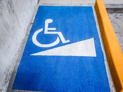Sign on ramp way of entrance to a public subway for disabled people.