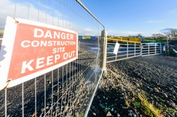 Sign on the fence of a construction site warning people to keep out