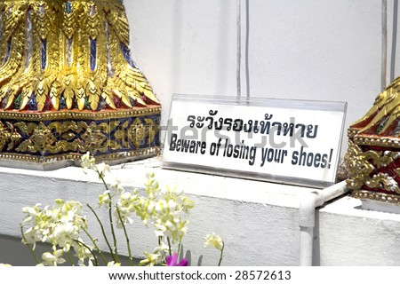 Sign outside buddhist temple in Bangkok, Thailand (etiquette demands removal of shoes at buddhist temples)