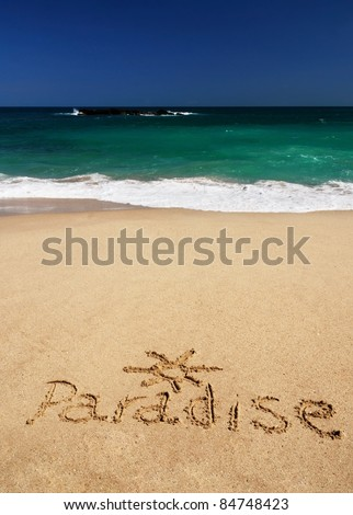 "Sign ""Paradise"" and drawing of the sun written in the sand of the tropical beach of Sri Lanka near the azure sea"