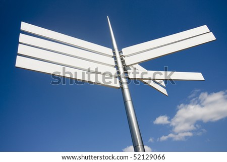 sign pointing in different directions against a blue sky