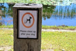 Sign post says 'Please clean up after your dog' at park in Australia.