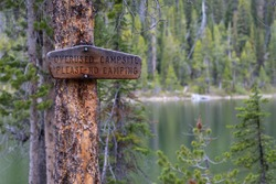 sign posted on a tree in central idaho of an overuse campsite at the lake