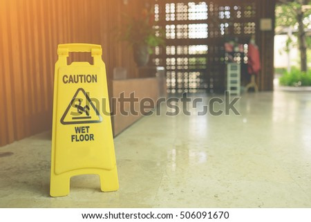 """Sign showing warning of caution wet floor,Lobby floor with """"caution wet floor"""" signs, selective focus on nearest sign.Sun flare effect.  #506091670"""