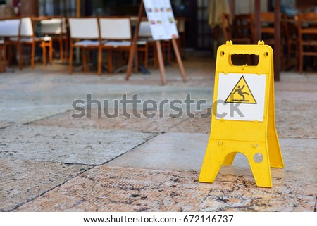 Sign showing warning of caution wet floor outdoors. #672146737