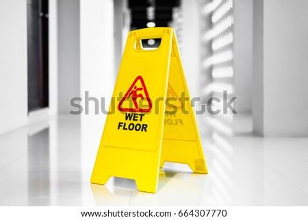 Sign showing warning of  wet floor on wet  floor  #664307770