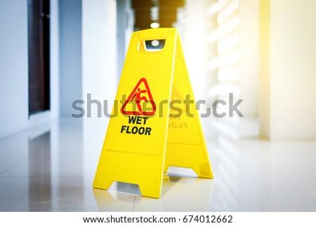 Sign showing warning of wet floor on wet floor in sunrise  #674012662