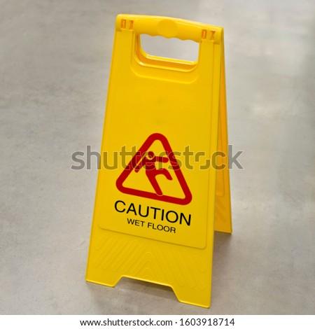 Sign showing warning of wet floor on wet floor. Wet floor caution sign on pathway in office.