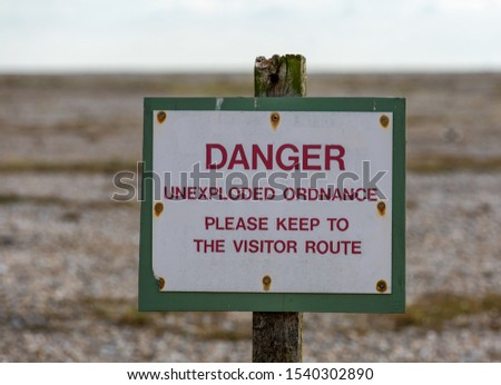 Sign to keep you to the path. ' Danger unexploded ordnance, please keep to the visitor route' Stock photo ©