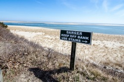 Sign warning visitors to keep off the bank and use the stairs at Cape Cod National Seashore on a sunny spring day. Seagrass and sand in the photo