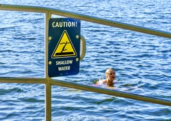 Sign warns about shallow water as warm weather brings more people to lakes and other water bodies, causing potential dangers