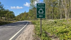 Sign waste facility with recycling logo and direction arrow by the side of rural road going through the forest.