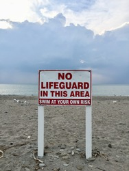 Sign with the words no lifeguard in this area swim at your own risk unscripted on white and red at a beach with sand rocks and seagulls blue water and blue sky