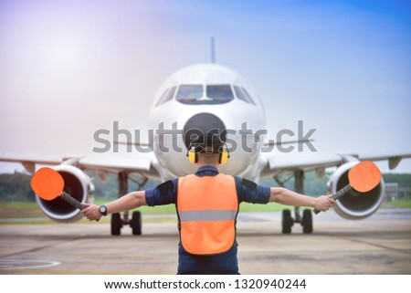 signal vest Aircraft. Airport officials are signaling the landing of the aircraft. #1320940244
